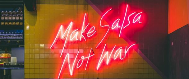 "neon sign saying ""Make salsa not war"""