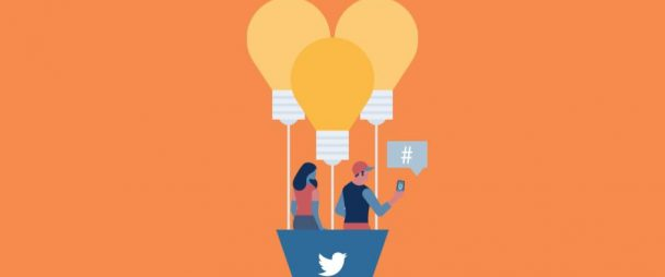 2 people in a hot air balloon with the Twitter logo on it. On person tweets from their phone.