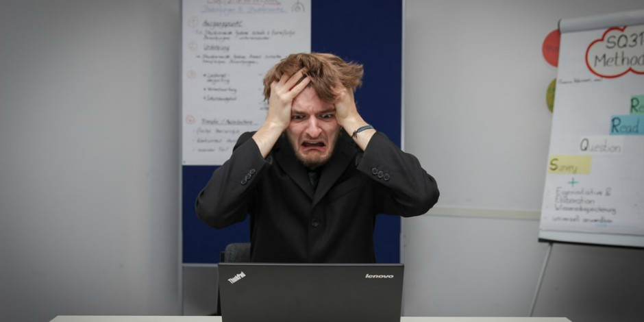 white man in front of laptop with hands on head looking scared and frustrated