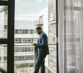 man in a blue suit standing on the balcony of a hotel room conducting business on his phone