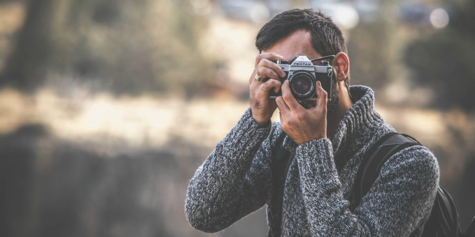 Sweater adorned man taking a photo of something