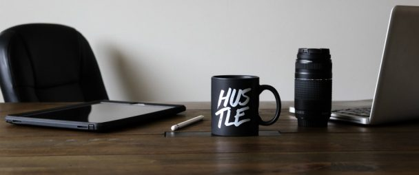 "desk with laptop, camera, and mug printed with ""hustle"""