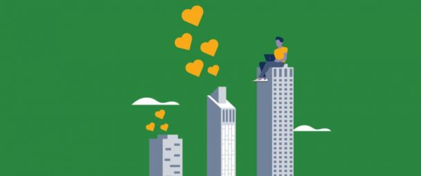 man typing on laptop on top of skyscraper, two more skyscrapers beside him with hearts comings out of the top