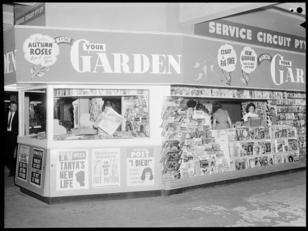 Black and white photo of a newspaper stand from the mid 20th century